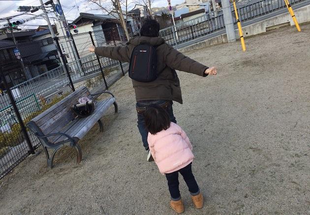 公園をリュックを背負って走り回る写真